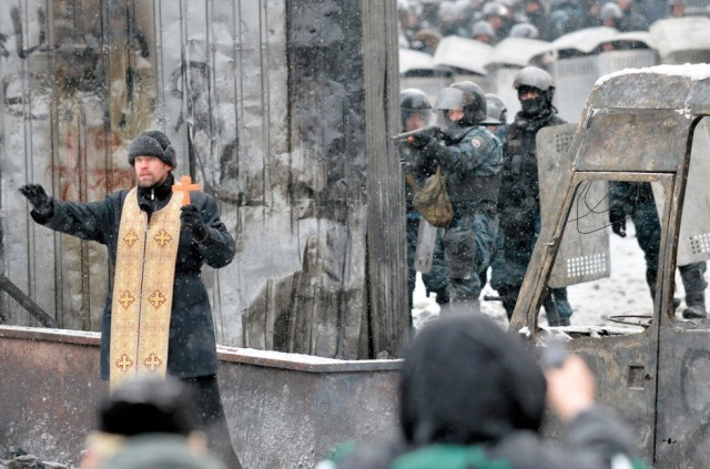 An orthodox priest stands between the people and the police.
